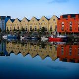 Edificios y barcos reflejados en el agua fotos de archivo