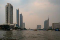 Edificios y opiniones del río sobre un fondo cubierto del cielo de la puesta del sol fotos de archivo