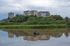 Edificios y vegetación reflejados en el río debajo del cielo cubierto Foto de archivo libre de regalías