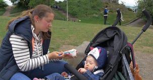 Edimburgo, Escócia - 1 Juny 2017: Bebê de alimentação da mãe no carrinho de bebê filme