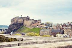 Edinburg inklusive slottcityscapen med dramatiska himlar Arkivfoto