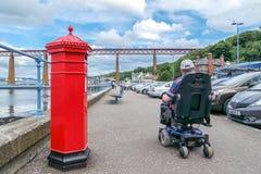 Edinburg Szkocja, Sierpień, - 26 2015: Mężczyzna w wózku inwalidzkim przechodzi listowego pudełko przy mostem Naprzód Zdjęcia Stock
