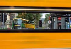 Edinburg turnerar bussen som ses till och med fönster av en Edinburgbuss, som den förbigår royaltyfri foto