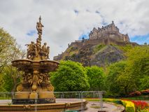 Edinburgh Castle and Ross Fountain seen from the Princes Street Gardens on a bright sunny day. Edinburgh Castle and Ross Fountain in Scotland, UK seen from the stock photos