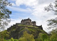 Edinburgh Castle. Sitting above the city on a large rock and framed by trees. The rock is a plug to an extinct volcano stock photos