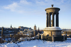 Edinburgh cityscape. View of edinburgh from snowy calton hill with castle in background and dugald stewart monument in fore Royalty Free Stock Photo