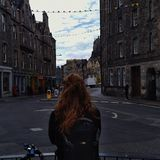 Edinburgh old town, an Irish girl looking out into the streets. Edinburgh is a mixture of Nordic roughness and medieval history, an Irish girl looking out into Stock Images