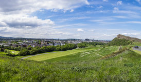 Edinburgh panorama from Holyrood Park. Panoramic summer view across Holyrood Park with Saisbury Crags looming over Edinburgh Scotland with the Castle on the Stock Photo
