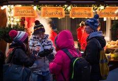 """EDINBURGH, SCHOTLAND, het UK †""""08 December, 2014 - Aziatische toeristenfamilie die van snel voedsel genieten bij Duitse Kerstmi Stock Afbeeldingen"""