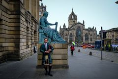 Edinburgh, Scotland - April 27, 2017: Bagpipe player with traditional scottish highlander robes playing on the Royal stock photography