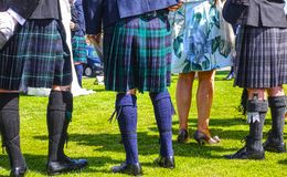 Edinburgh, people wearing traditional Scottish kilts. EDINBURGH, SCOTLAND - JULY 14, 2017: People wearing traditional Scottish kilts, stockings, dress shoes and royalty free stock images