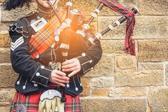 EDINBURGH, SCOTLAND, 24 March 2018 , Scottish bagpiper dressed i. N traditional red and black tartan dress stand before stone wall. Edinburgh, the most popular stock photos