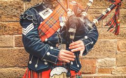 EDINBURGH, SCOTLAND, 24 March 2018 , Scottish bagpiper dressed i. N traditional red and black tartan dress stand before stone wall. Edinburgh, the most popular royalty free stock photography