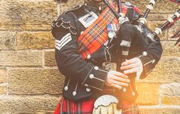 EDINBURGH, SCOTLAND, 24 March 2018 , Scottish bagpiper dressed i. N traditional red and black tartan dress stand before stone wall. Edinburgh, the most popular stock photography