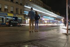 Traffic at night in the city of Edinburgh. EDINBURGH, UK - CIRCA AUGUST 2015: Traffic at night in the city of Edinburgh with a couple waiting to cross the street Stock Photography
