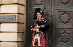 Busking bagpiper on the street in Edinburgh. EDINBURGH, UK - DECEMBER 09 2017: The busking man plays bagpipe on the street on December 09,2017 in Edinburgh, UK royalty free stock photo