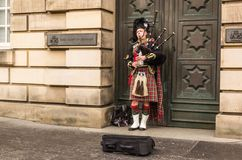 Busking bagpiper on the street in Edinburgh. EDINBURGH, UK - DECEMBER 09 2017: The busking man plays bagpipe on the street on December 09,2017 in Edinburgh, UK stock photography