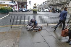 Homeless man sitting on the pavement Royalty Free Stock Photography