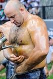 EDIRNE TURCJA, LIPIEC, - 06, 2013: Zapaśnik dostaje oliwa z oliwek przed rywalizacją w tradycyjnym Kirkpinar zapaśnictwie KırkpÄ Obraz Royalty Free