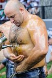 EDIRNE, TURKEY - JULY 06, 2013: Wrestler getting olive oil before competition in traditional Kirkpinar wrestling. Kırkpınar is a Royalty Free Stock Image
