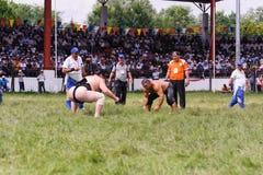 EDIRNE TURKIET - JULI 26, 2010: Pehlivan för brottare turkisk och japansk sumobrottare på konkurrensen i Kirkpinar Kirkpinar I Arkivfoton