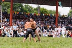 EDIRNE TURKIET - JULI 26, 2010: Pehlivan för brottare turkisk och japansk sumobrottare på konkurrensen i Kirkpinar Kirkpinar I Royaltyfri Bild