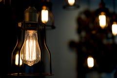 Edison żarówka jarzy się w ciemnym zamazanym tle Fotografia Stock