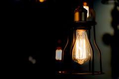 Edison żarówka jarzy się w ciemnym zamazanym tle Obraz Stock