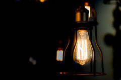 Edison bulb glowing in the dark blurred background Stock Image