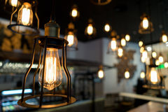 Edison bulb glowing in the dark blurred background Royalty Free Stock Image