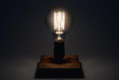 Edison Lamp con il filamento su un supporto di legno Concetto del faro Immagine Stock