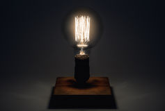 Edison Lamp with filament on a wooden stand. Lighthouse concept Stock Image