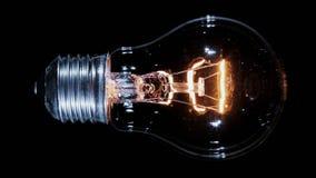 Edison lamp light bulb blinking over black, macro view stock video