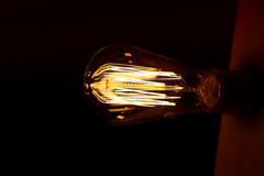 Edison light bulb hanging on a long wire. Cozy warm yellow light.Retro Royalty Free Stock Images