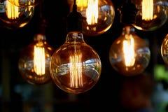 Edison light bulb hanging on a long wire. Cozy warm yellow light.Retro stock image