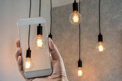 Edison`s light bulb. Hand holind smart phone at Edison`s light bulb Royalty Free Stock Photos