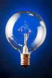 Edison's lit filament bulb. Edison's round filament bulb, upright on blue gradient background Royalty Free Stock Photo