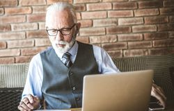 Edit the document before signing. Senior business man using laptop and reading document. Close up stock photos