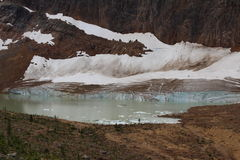 Edith Cavell Pond. Turquoise meltwater of Cavell pond sitting below the jagged summit of Mount Edith Cavell is one of the beautiful setting in Jasper National stock photography