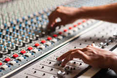 Editor adjusting the sound mixer. An expert adjusting audio mixing console Royalty Free Stock Photos