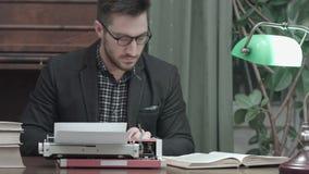 Editor concentrado que verifica a informação no livro e que datilografa na máquina de escrever vermelha do vintage vídeos de arquivo