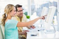 Editor de fotos alegre que aponta em um computador Fotos de Stock Royalty Free