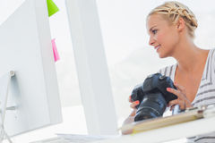 Editor de fotos atractivo que mira una cámara digital fotos de archivo libres de regalías