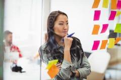 Editor de fotos de sexo femenino que mira notas pegajosas coloreadas multi Imagen de archivo