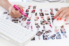 Editor de fotos de sexo femenino que trabaja en una hoja del contacto fotos de archivo