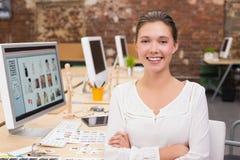 Editor de fotos fêmea de sorriso no escritório Fotografia de Stock Royalty Free