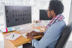 Editor de fotos hermoso que trabaja en el ordenador fotos de archivo