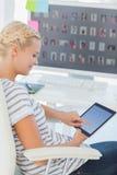 Editor de fotos louro bonito que trabalha em um tablet pc foto de stock royalty free
