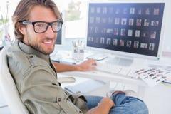 Editor de fotos que da vuelta y que sonríe en su escritorio imágenes de archivo libres de regalías