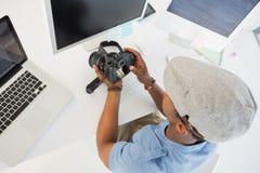 Editor de fotos que mira la cámara digital en oficina imagen de archivo libre de regalías